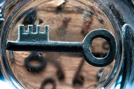 Old rusty key on the bottom of glass of water Stock Photo