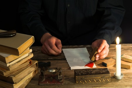 sealing: Man writing a letter with quill and sealing. Vintage Stock Photo