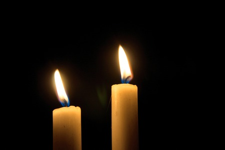 Two burning candles on black background. Copyspace