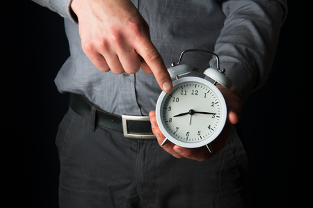 reminding: Businessman holding a clock reminding about deadline Stock Photo