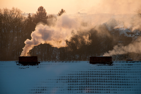 Roofs covered with snow at sunrise. Smoke from the chimneys