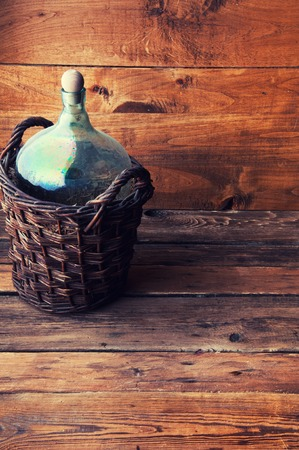 Carboy in wicker basket on wooden table, copyspace