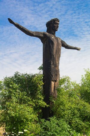 Side view picture of a wooden statue of Jesus who is standing in full pose with spread arms with a blue sky in the background Archivio Fotografico