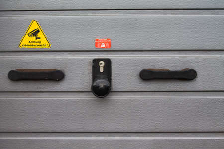"""Texture of an aluminum garage door. With handle and lock and a sticker with a warning """"video monitored"""""""