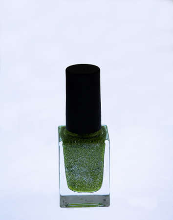 A bottle of green nail polish with mica in an isolated picture. Banco de Imagens