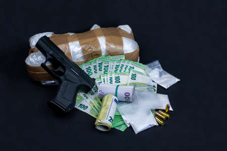 Gun, euro notes and drugs. The money open and rolled. The drugs packed in bags. Individual 9mm cartridges are included.