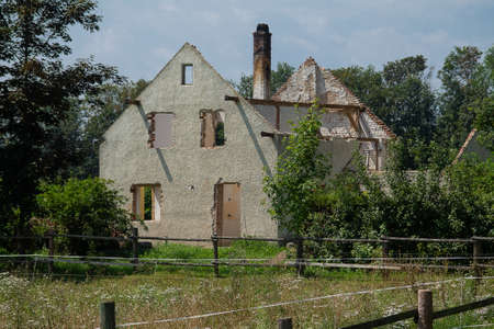 An old house with the windows, doors and roof including the roof truss removed. A ruined building.