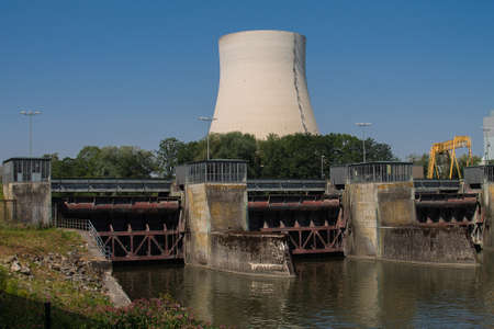 Three locks of a hydropower plant with a machine house. And a cooling tower of a nuclear power plant in the background.