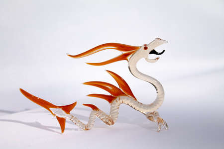 Murano mouth blown dragon. Clear body, orange bone plates and eyes, black tongue.