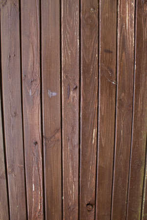 Texture of an old brown wooden wall. The slats are installed vertically.