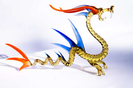 Murano mouth blown dragon. Clear golden body, orange and blue bone plates and eyes, white teeth.