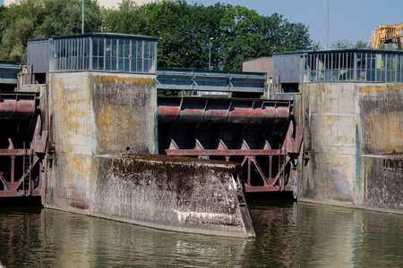 A floodgate of a hydropower plant with a machine house. Stok Fotoğraf