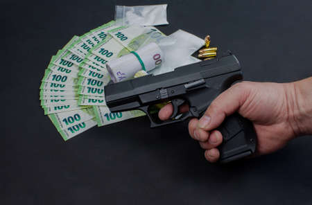 Gun, euro banknotes and drugs. The money opened and rolled. The drugs packed in bags. Individual 9 mm cartridges are included. The weapon is held in one hand.