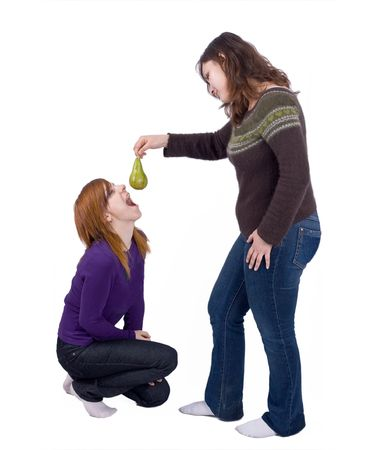 domination: isolated girl playfully offers a pear fruit to another kneeling one