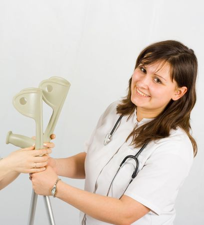 positive woman hands crutches to her patient photo