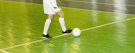 Football or Soccer player controlling the ball on a green indoor court.