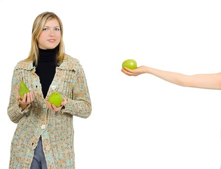 one girl gives an apple to a another who already has an apple and a pear in her hands photo