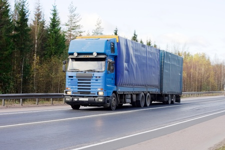 tractor trailer truck on background of trees