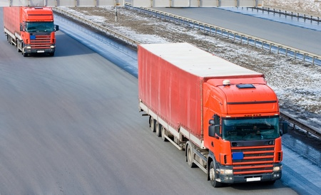 Two red tractor trailer trucks photo