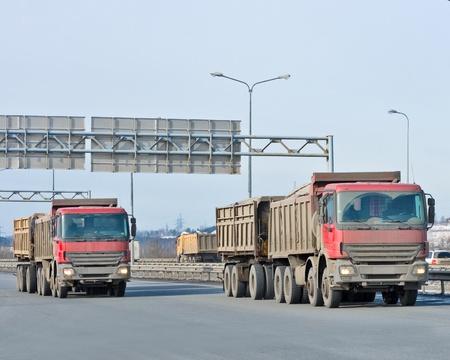 wheeler: Red dump trucks ride in a line