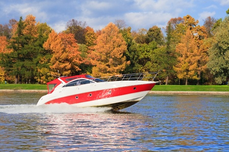 green boat: Speed boat riding by a river bank Stock Photo