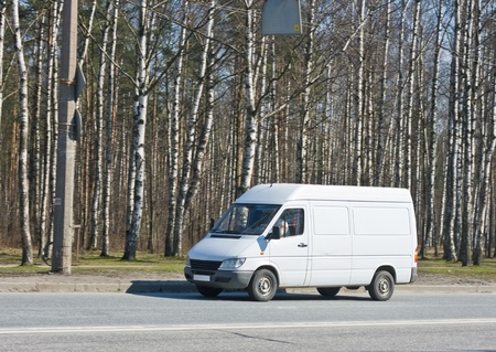 blank van drives by a forest photo
