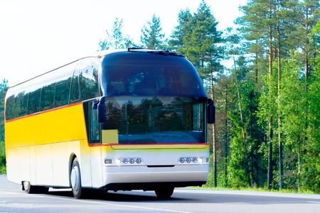 business trip: yellow bus on a forest road - of Buses series Stock Photo