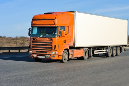 orange truck with white container on road