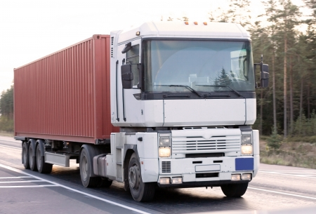 Bright red container truck on road