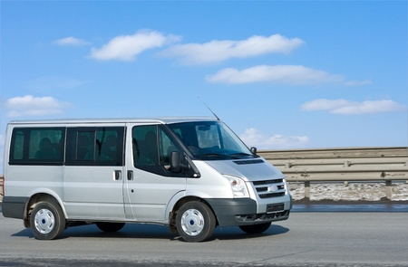 silver van on road with blue horizon on the background