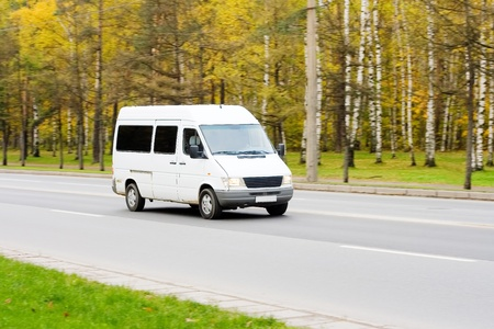 mini small passenger Tour van bus on road isolated   photo