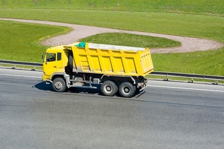 haul: yellow dump truck on a highway Stock Photo