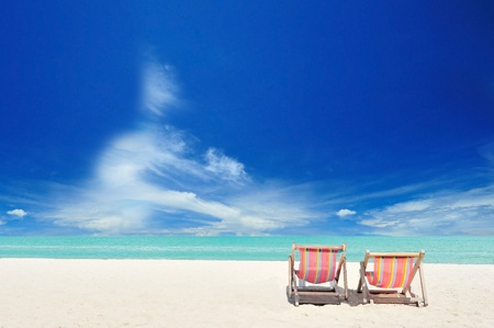 Beach chairs on the white sand beach with cloudy blue sky Stock Photo