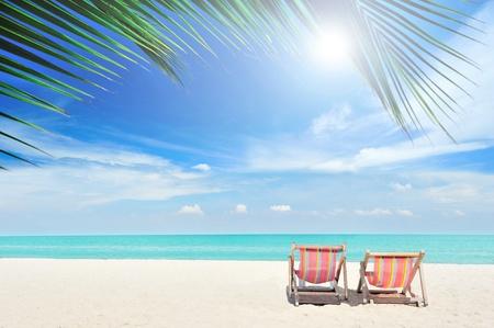 Sillas de playa en la playa de arena blanca con el cielo azul nublado