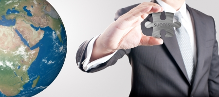 Business man showing metal jigsaw puzzle piece with  SUCCESS  wording with realistic globe in background  Concept for business strength and success  Elements of this image furnished by NASA  photo