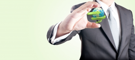Business man showing Realistic globe with spiral green arrow for recycle and eco concept  Elements of this image furnished by NASA photo