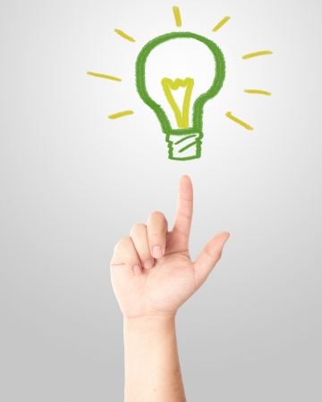 Hand pointing to the hand draw green light bulb  Concept for new idea  Stock Photo