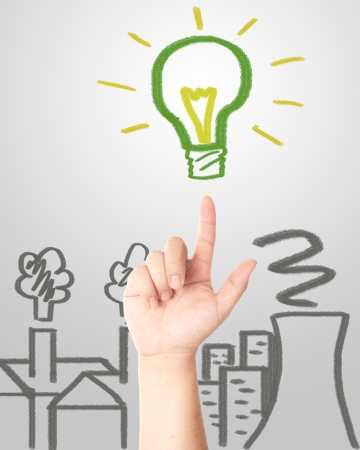 Hand pointing to the hand draw green light bulb with factories and Nuclear plant pollution  Concept for eco and global warming