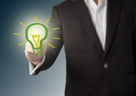 Stock Photo  Businessman with a pen in hand drawing light bulb  Concept for new idea  photo