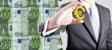 Business man holding euro currency sign with euro bank note in jigsaw style background  Concept for Euro economic crisis