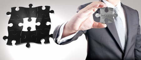 Business man showing missing metal jigsaw puzzle piece with  SUCCESS  wording  Concept for business strength and success