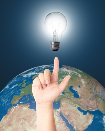 Hand pointing Light bulb with realistic earth in background for eco and power saving concept  Elements of this image furnished by NASA  Stock Photo