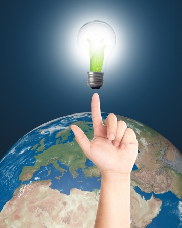 Hand pointing Light bulb with leaves inside and realistic earth in background for eco and power saving concept  Elements of this image furnished by NASA