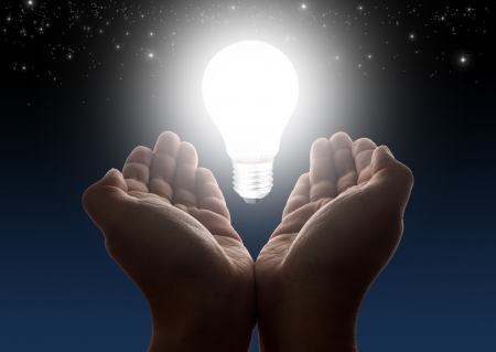 glowing light bulb: Hands holding light bulb with night sky and stars in background Stock Photo