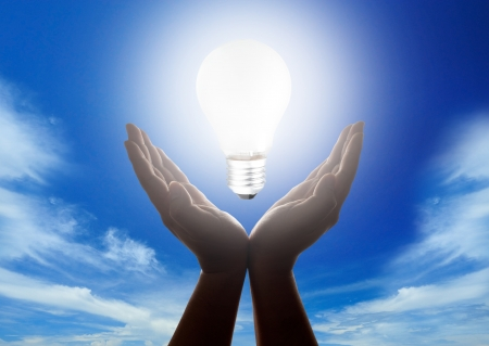 Hands holding light bulb with cloudy blue sky in background