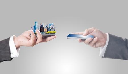 garden city: Los hombres de negocios la celebraci�n de tel�fono inteligente con la ciudad en la pantalla para el concepto de negocio de comercio