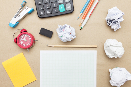rubber sheet: Business concept:Calculator,stapler,red clock,white blank paper,crumpled paper,post it and color pencil,pencil,pen on brown paper background Stock Photo
