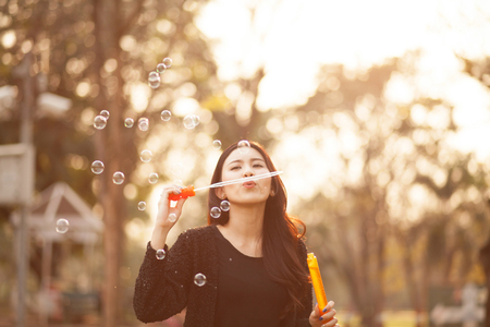 Pretty Thai girl blowing a bubbles at the park Stock Photo