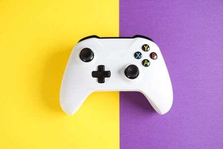 Computer gaming competition. Gaming concept. White joysticks on yellow and purple background. Stock Photo