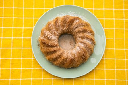 A delicious home made cake. Tasty home made cake in a plate on a yellow tablecloth.